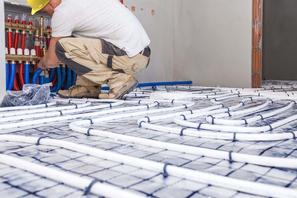 man installing underfloor heating