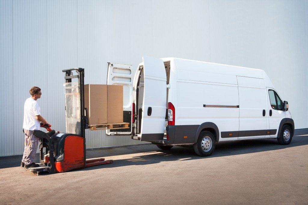 man putting boxes in sprinter van