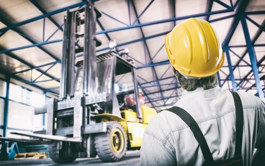 man looking at crane lifting boxes