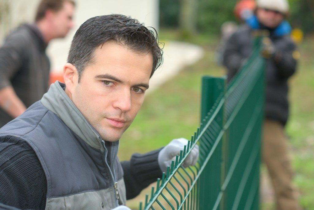 men building fence