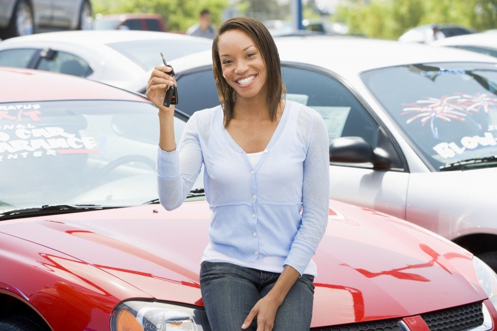 Woman picking up used car from lot