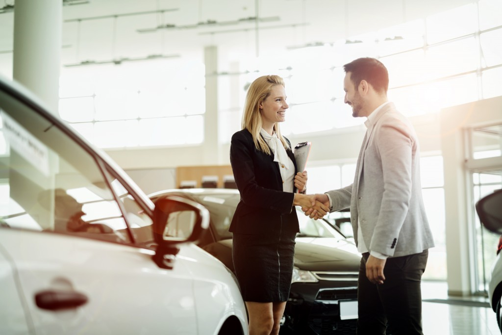 Salesperson with a client at a car dealership