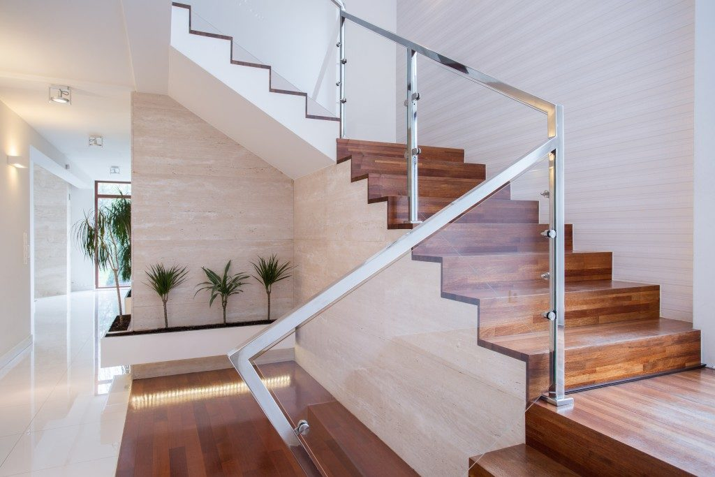 wooden staircase with glass and metal side
