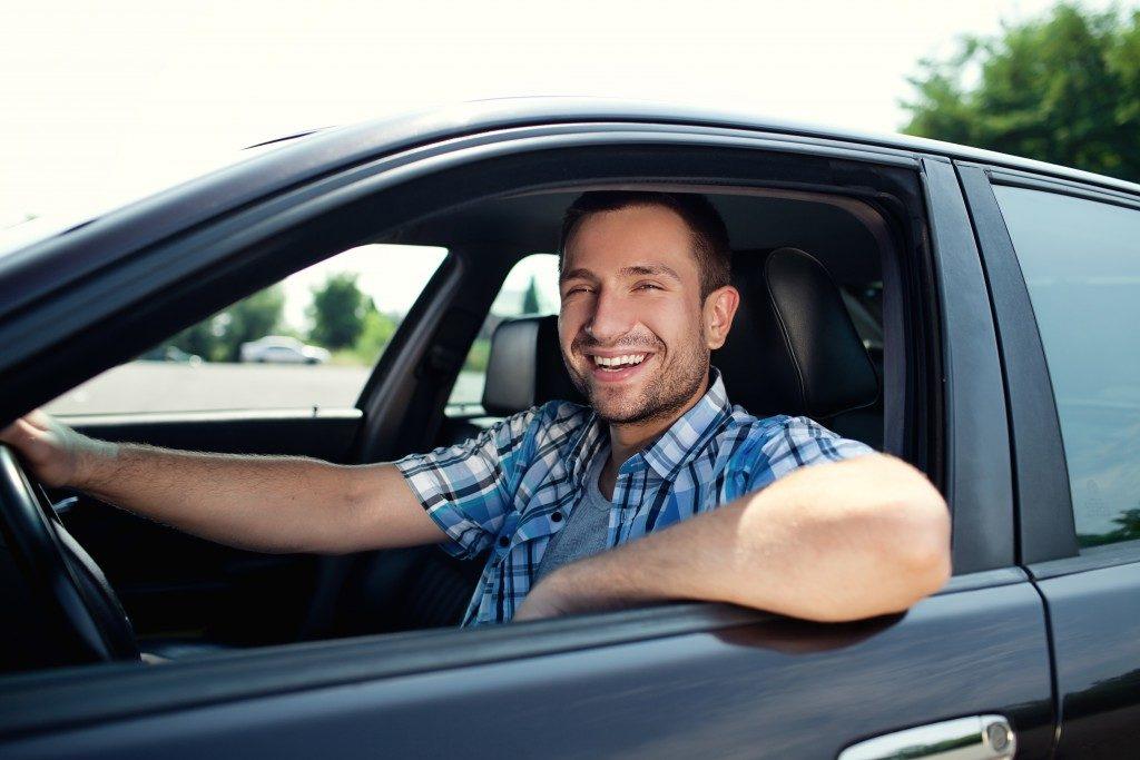 man smiling while driving car
