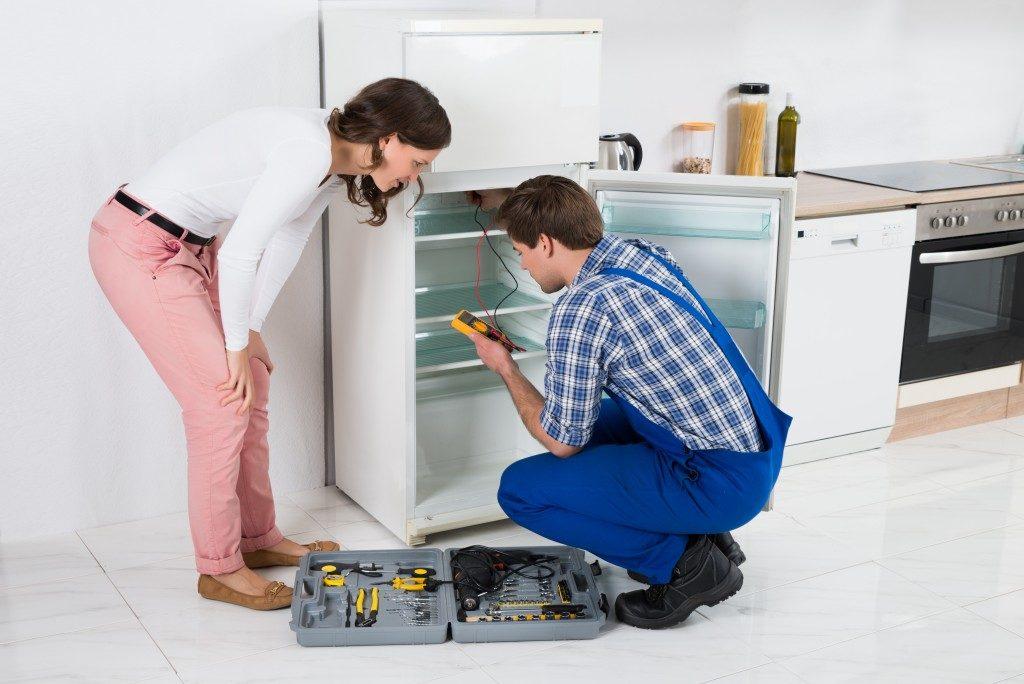 housewife looking at worker repairing the fridge
