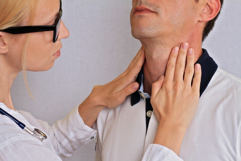 female doctor checking neck and thyroid area of man