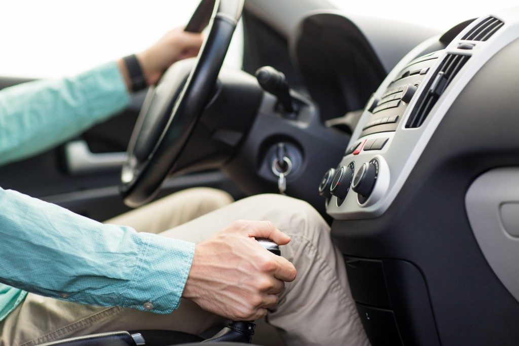 driver holding the wheel and gear stick