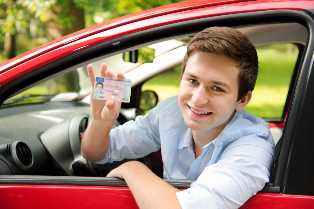 teenager sitting in new car and showing his driver's license