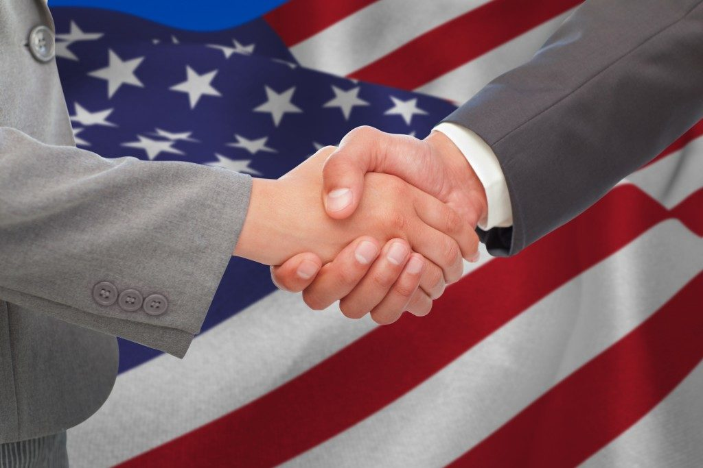 men shaking hands and the american flag