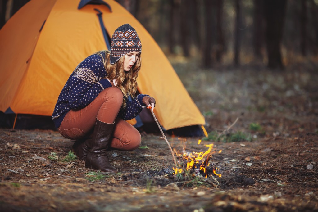woman making a fire at the camp site