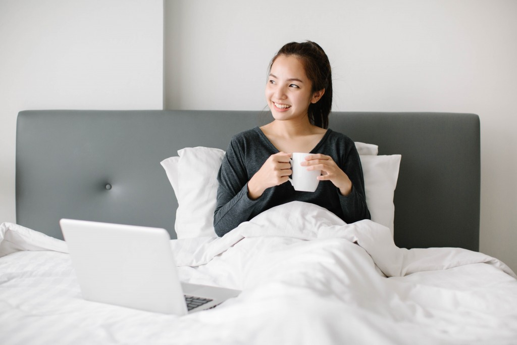 millenial in bed with coffee and laptop