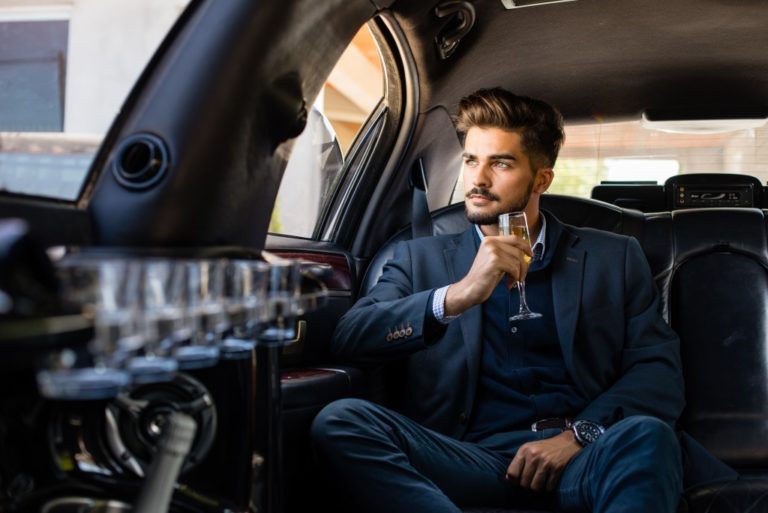 man drinking champagne in the limo