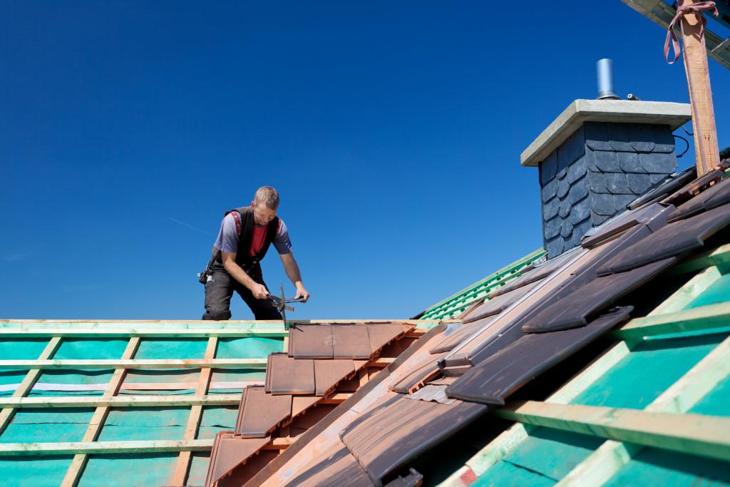 man installing roof tiles