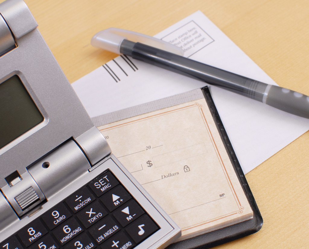 calculator, calendar, a piece of paper, and a pen on a table